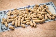 Hölzerne Kugeln mit einem Geld auf einem hölzernen Hintergrund Biologische Brennstoffe Katze lizenzfreies stockbild