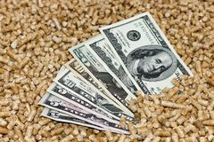 Hölzerne Kugeln und Geld, Dollar Das Konzept von Einsparungen, wenn biologische Brennstoffe von den Holzspänen verwendet werden D stockfotos
