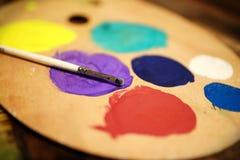 Hölzerne Kunstpalette mit Farbe und Bürste auf Weinlesehintergrund Stockfoto