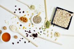 Hölzerne Löffel auf der linken Seite, voll von den Samen und von den Getreide stockfoto