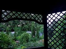 Hölzerne Laube mit Gitter im Häuschenblumengarten stockbilder