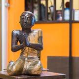 Hölzerne Mönchskulptur, die Sawasdee tut (Respekt zahlend) stockfotografie