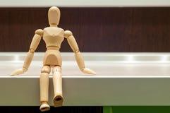 Hölzerne Mannequin- oder Mannfigürchen, die auf Weiß sitzt Lizenzfreies Stockfoto
