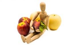 Hölzerne Mannmarionette mit Frucht Stockfoto