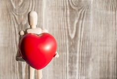 Hölzerne Mannzahl, die einen roten Herzball hält stockfoto