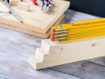 Hölzerne Materialien und gelber Bleistift des messenden Meters Lizenzfreies Stockbild