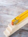 Hölzerne Materialien und gelber Bleistift des messenden Meters Lizenzfreies Stockfoto