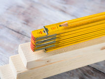 Hölzerne Materialien und gelber Bleistift des messenden Meters Lizenzfreie Stockfotos