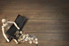 Hölzerne menschliche Figürchen, leere schwarze Geldbörse und englische Münzen, Ove Stockfoto
