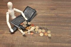 Hölzerne menschliche Figürchen, leere schwarze Geldbörse und englische Münzen, Ove Lizenzfreie Stockfotos
