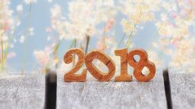 Hölzerne Nr. 2018 auf Planke und Unschärfe bedeckt Blumenhintergrund mit Gras Lizenzfreie Stockfotos