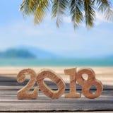 Hölzerne Nr. 2018 auf Planken auf tropischem Strandhintergrund Stockfotos