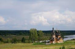 Hölzerne orthodoxe Kirche auf einer Flussquerneigung Stockfotos