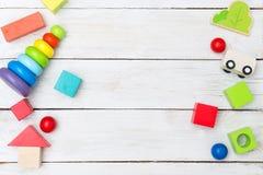 Hölzerne pädagogische Mehrfarbenspielwaren auf einem hölzernen Hintergrund flach Lizenzfreie Stockfotos