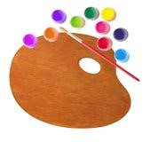 Hölzerne Palette mit Farbfarben und Bürste lokalisiert auf Weiß Lizenzfreie Stockfotografie