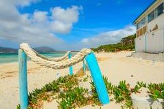 Hölzerne Pfosten und Strandbar durch das Meer in Sardinien Lizenzfreie Stockbilder