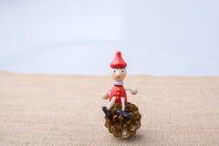Hölzerne Pinocchio-Puppe, die auf Kiefernkegel sitzt Stockfotografie