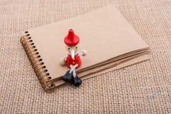 Hölzerne Pinocchio-Puppe, die auf Notizbuch sitzt Stockbild