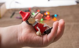 Hölzerne Pinocchio-Puppe, die in der Hand sitzt Stockbild