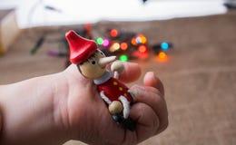 Hölzerne Pinocchio-Puppe, die in der Hand sitzt Lizenzfreies Stockfoto