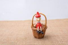 Hölzerne Pinocchio-Puppe, die Minikorb sitzt Stockbilder