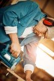 Hölzerne Planke des Mannausschnitts unter Verwendung der elektrischen Spannvorrichtung sah Lizenzfreie Stockfotografie