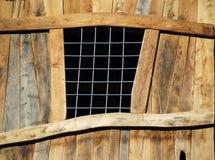 Hölzerne Plankenwand mit Drahtfenster Stockfoto