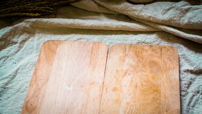 Hölzerne Platte, auf der natürlichen Leinenabdeckungstabelle, die Nahrungsmittelmenüidee kocht stockfoto
