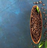 Hölzerne Platte in Form von der Boote dunklen aromatischen Kaffeebohnen voll auf einem bunten blaugrünen Hintergrund stockbild