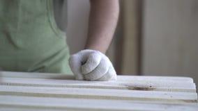 Hölzerne Produkte werden durch den Meister in den weißen Handschuhen und in einem grünen Schutzblech verarbeitet Arbeiten mit Hol stock footage