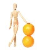 Hölzerne Puppe und Orangen auf einem weißen Hintergrund Stockfotografie