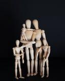 Hölzerne Puppen der Fotos, glückliche Familie mit Kindern auf schwarzem Hintergrund Stockfotos