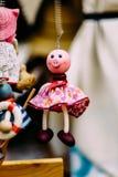 Hölzerne Puppen gekleidet in den verschiedenen Ausstattungen handgemachte hölzerne Puppen, die als Anzeige hängen Dekorative Pupp Lizenzfreie Stockfotos