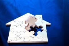 Hölzerne Puzzlespielwartezeit, zum der Hauptform für Gestalttraumhaus oder des glücklichen Lebenkonzeptes für Eigentum zu erfülle stockbilder