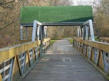 Hölzerne Radfahrenbrücke mit grüner Dachhaube Stockbilder