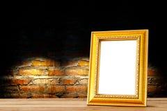 Hölzerne Regale des goldenen hölzernen Fotorahmens gegen Backsteinmauer Stockfoto