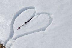 Hölzerne Rosenkranzperlen auf dem Herzen gezeichnet in den Schnee Stockbild