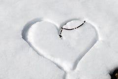 Hölzerne Rosenkranzperlen auf dem Herzen gezeichnet in den Schnee Lizenzfreies Stockbild