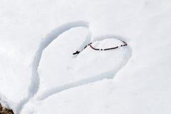 Hölzerne Rosenkranzperlen auf dem Herzen gezeichnet in den Schnee Lizenzfreies Stockfoto