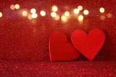 Hölzerne rote Herzen auf rotem glänzendem Hintergrund Lizenzfreies Stockbild