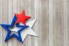 Hölzerne rote, weiße und blaue Sterne auf einem rustikalen Hintergrund mit Kopie sperren,/4. des Juli-Hintergrundkonzeptes stockfotos