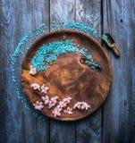 Hölzerne rustical Schüssel mit Seesalz, -schaufel und -blumen auf blauer Tabelle, Wellnesshintergrund, Draufsicht Lizenzfreie Stockbilder