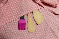 Hölzerne Schöpflöffel- und Silikonbürste auf rosa Gitter Stoff Lizenzfreie Stockbilder