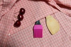 Hölzerne Schöpflöffel- und Silikonbürste auf rosa Gitter Stoff Mit Kirsche drei Lizenzfreies Stockfoto