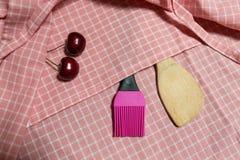 Hölzerne Schöpflöffel- und Silikonbürste auf rosa Gitter Stoff Mit Kirsche zwei Lizenzfreies Stockbild