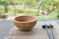 Hölzerne Schüssel mit Essstäbchen auf Bambusmatte auf Holztisch im Garten Stockbild