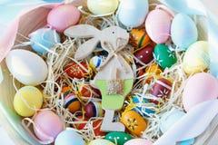 Hölzerne Schüssel mit Orange, gelb, Rosa und grünen Eiern auf weißem hölzernem Hintergrund Fröhliche Ostern! Dekoration stockfotos