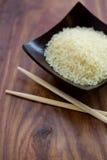 Hölzerne Schüssel mit Reis und chinesischen Essstäbchen Stockfoto