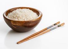Hölzerne Schüssel mit Reis und Essstäbchen Stockfoto