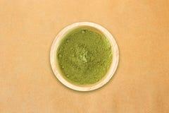 Hölzerne Schüssel Pulver des grünen Tees auf Hintergrund des braunen Papiers Lizenzfreies Stockfoto